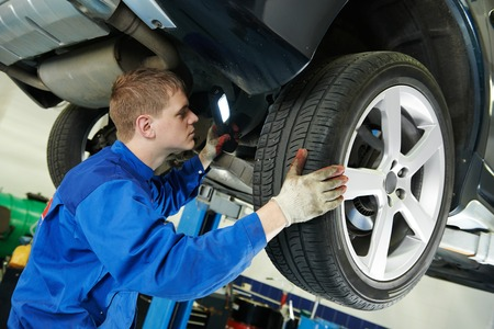 motor mechanic: car mechanic examining car suspension of lifted automobile at repair service station