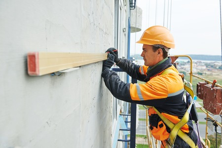 steeplejack: Facade worker builder working with level at ventilation facade construction on a building