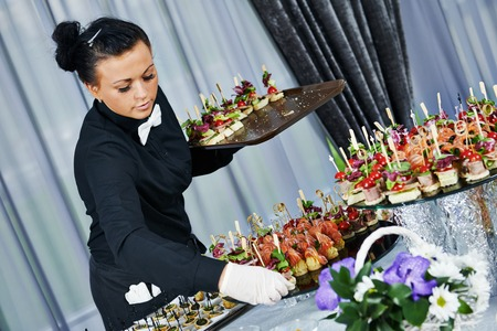 Waiter with meat dish serving catering table with food snacks during party event photo