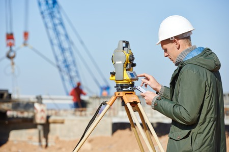 exact position: Surveyor builder worker with theodolite transit equipment at construction site outdoors during surveying work