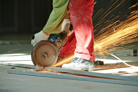 mounter: Construction builder worker with grinder machine cutting metal bar at building site