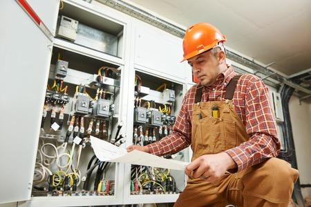 electricista: trabajador constructor ingeniero electricista adulto con plan de esquema el�ctrico en frente de la Junta de interruptor de fusible