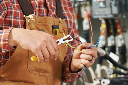 electric power: hands of electrician builder engineer worker with electric equipment and wire