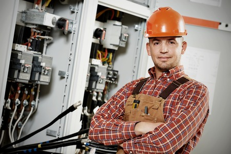 electricista: adulto joven electricista trabajador ingeniero constructor delante de placa del interruptor de fusibles Foto de archivo
