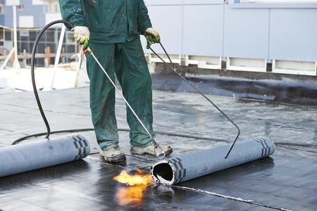 Roofer Installation Dachpappe mit Erhitzen und Schmelzen von Bitumen Rolle von Fackel Flamme während Dachreparatur
