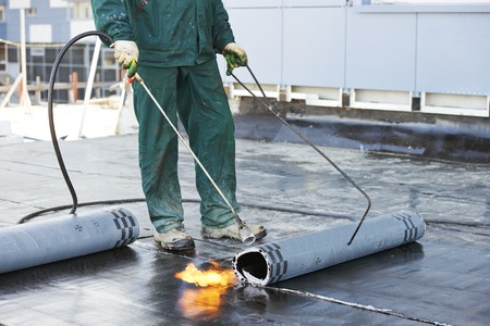 Roofer installing Roofing felt with heating and melting of bitumen roll by torch on flame during roof repair photo