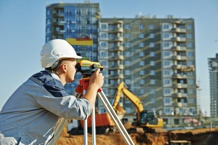 teodolito: Trabajador de construcción Topógrafo con equipos de tránsito teodolito en el sitio de construcción al aire libre durante el trabajo de topografía