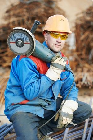 molinillo: Constructor de la construcción Retrato del trabajador con la máquina amoladora para cortar barras de refuerzo de barras de refuerzo de metal en el sitio de construcción Foto de archivo