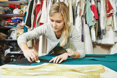 costumes: young female tailor working with cloth fabric in workshop Stock Photo