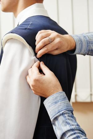 男性の仕立て屋デザイナー オーダーメイドのスーツのフィッティング中にジャケットをマークを作る