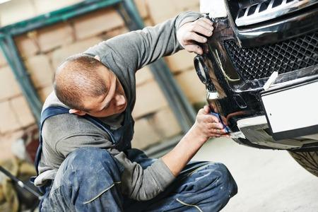 car repair shop: auto mechanic worker sanding polishing bumper car at automobile repair and renew service station shop by sandpaper
