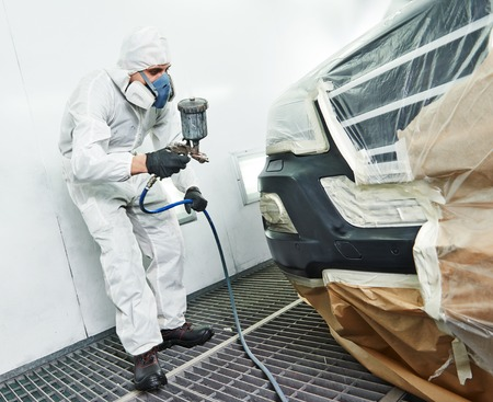 automobile repairman painter painting car body bumper in chamber photo