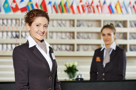 Happy female receptionist worker standing at hotel counter Stock Photo
