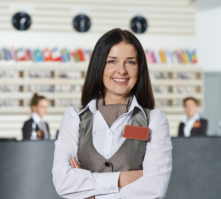 Happy female manager worker standing at hotel Foto de archivo
