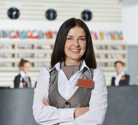 profesionistas: Trabajador encargado de sexo femenino feliz que se coloca en el hotel