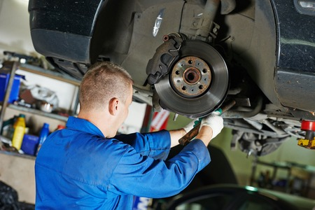 car mechanic worker repairing suspension of lifted automobile at auto repair garage shop station Stockfoto