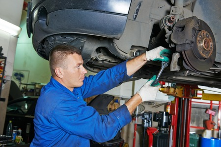 suspension: car mechanic worker repairing suspension of lifted automobile at auto repair garage shop station Stock Photo