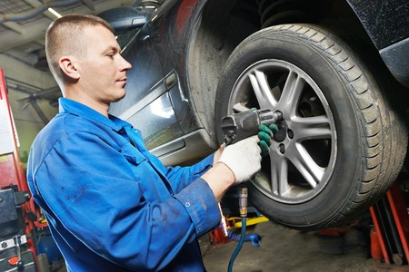 disassembly: car mechanic screwing or unscrewing car wheel of lifted automobile by pneumatic wrench at repair service station