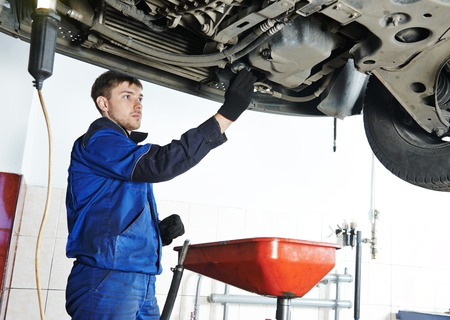 Car servicing, replacing of motor oil and filter at auto repair shop photo