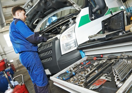 auto repairman industry mechanic worker servicing car auto in repair or maintenance shop service station photo