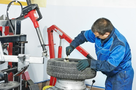 tire fitting: Auto repairman lubricating automobile car wheel during tyre fitting or tire replacing