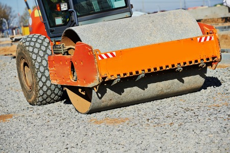 roadwork: Heavy vibration roller compactor at urban road construction and repairing asphalt pavement works Stock Photo