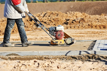 compacting: builder worker at sand ground compaction with vibration plate compactor machine before pavement roadwork