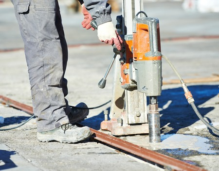 the hole: concrete boring with industrial drilling machine on building construction site