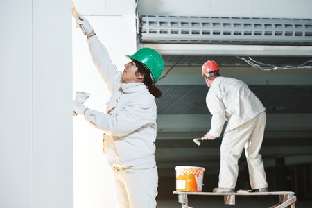 plasterer and painter at indoor wall renovation decoration with spatula and plaster