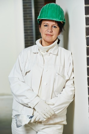 Portrait of plasterer at indoor wall renovation decoration with palette knife