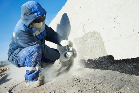 Builder worker with grinder machine cutting metal parts at construction site Stock Photo