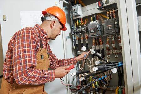 electricidad: adulto joven electricista trabajador ingeniero constructor delante de placa del interruptor de fusibles Foto de archivo