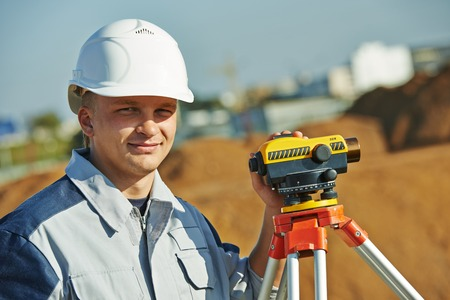 tachymeter: Surveyor builder worker with level equipment at construction site outdoors during surveying work