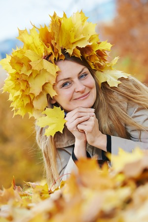 Smiling adult woman with autumn maple leaves wreath in park at fall outdoors photo