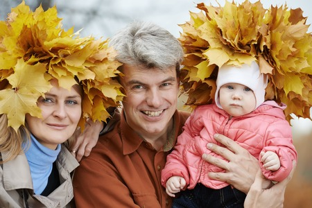 Smiling family with woman with autumn maple leaves wreath in park at fall outdoors photo
