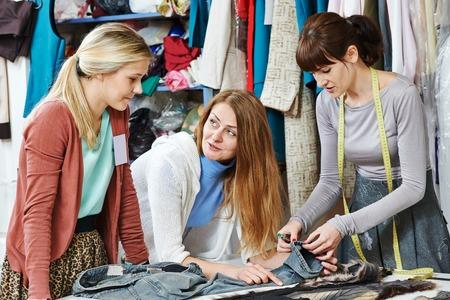 vrouwelijke kleermaker werknemers, modelbouwer en stylist bespreken kleding ontwerp in werkplaats
