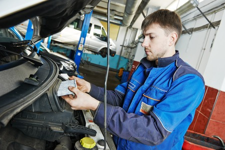 Car servicing, replacing air filter maintenance at auto repair shop Stock Photo