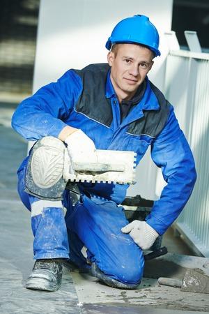 tiler: Portrait of industrial tiler builder worker installing floor tile at repair renovation work