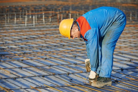 builder worker knitting metal rebars into framework reinforcement for concrete pouring at construction site photo