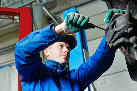 car mechanic worker repairing suspension of lifted automobile at auto repair garage shop station Stock Photo
