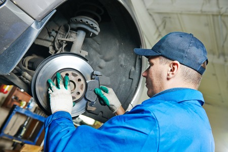 car mechanic worker replacing brakes of lifted automobile at auto repair garage shop station Stockfoto