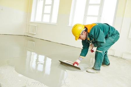 plasterer during floor covering works with self-levelling cement mortar photo