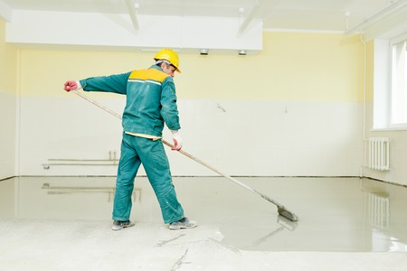 floor covering: plasterer during floor covering works with self-levelling cement mortar