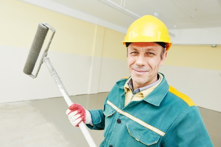 floor covering: male plasterer portrait during floor covering works with self-levelling cement mortar Stock Photo
