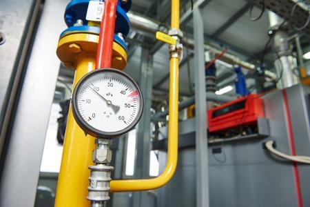 Válvulas Primer del manómetro, tuberías y grifos de sistema de calefacción de gas en una sala de calderas