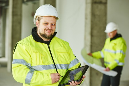 young male construction engeneer worker project manager with tablet pc at a indoors building site Stockfoto