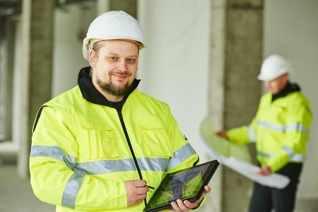 joven ingeniero director del proyecto de construcción trabajador hombre con tablet pc en una obra de construcción en el interior Foto de archivo