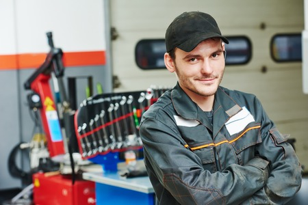 scheduled replacement: repairman auto mechanic portrait in car auto repair or maintenance shop service station
