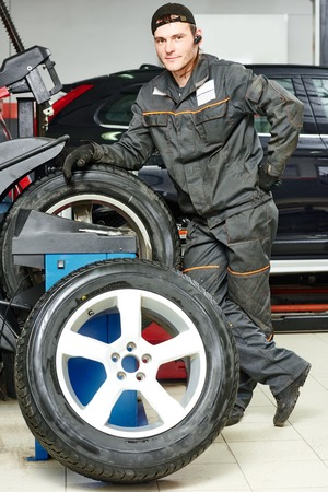 tire fitting: Auto repairman with automobile car wheel at tyre fitting machine during tire replacing Stock Photo