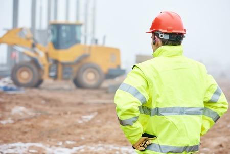 Stavební mistr dělník se dívá na stavební práce na místě